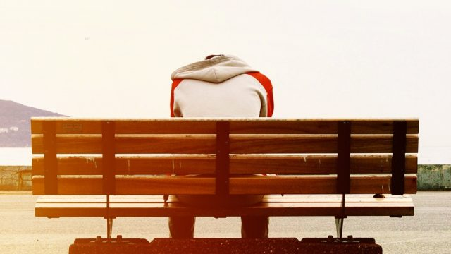 A man sitting alone on a bench